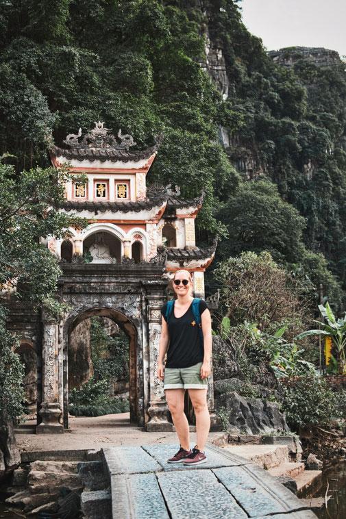 Frau steht auf einer Steinbrücke vor einem Eingangstor zum Tempel