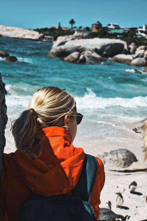 Steffi schaut auf den Boulders Beach mit Pinguinen im Hintergrund, Südafrika