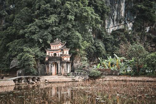 Eingang zum Tempel. Vor dem Tor eine kleine Steinbrücke, im Hintergrund riesige Karstfelsen