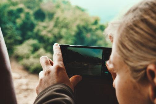 Frau macht Bild mit einem iPhone am Ufer des Mekongs