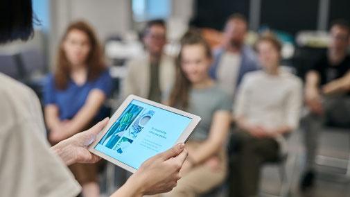 Seminarteilnehmer sitzen in einem Raum und hören dem Seminarleiter zu, der ein Tablet in der Hand hält