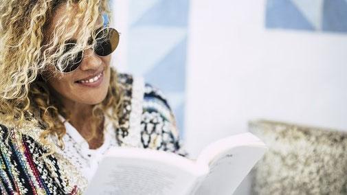 Frau mit wilden blonden Locken und Sonnenbrille lernt zu Hause aus einem Buch für ein Seminar