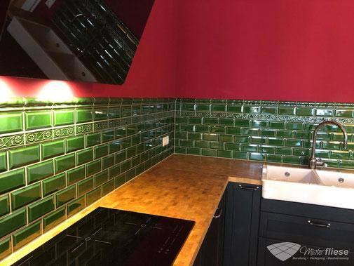 Küchenfliesenspiegel im grünen Metrogedesign, kombiniert mit einer roten Küchenwand
