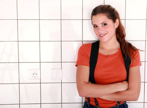 Frau vor gefliester Wand.