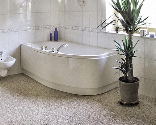 Badezimmer mit Badewanne und verlegtem Steinteppich.