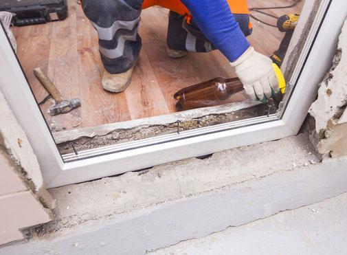 Monteur beim Einbau einer Tür oder eines Fensters.