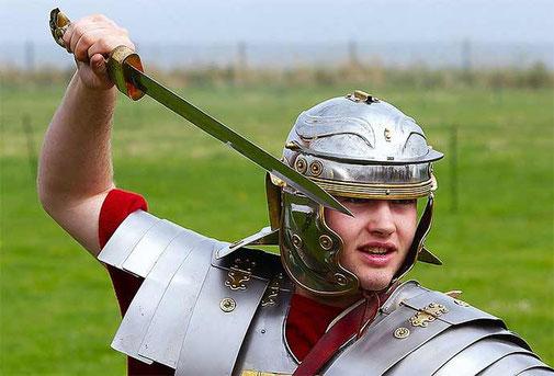 Reconstitution d'un légionnaire romain en armure tenant un glaive.