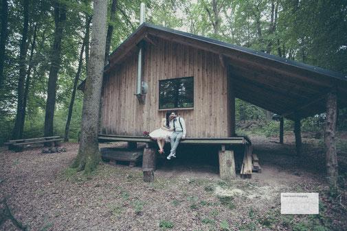 Ein Hochzeitspaar sitzt vor einem Holzhaus an der Hochzeitslocation Kletterpark des Outdoor Zentrums Lahnstein fotografiert vom Hochzeitsfotograf Hanau