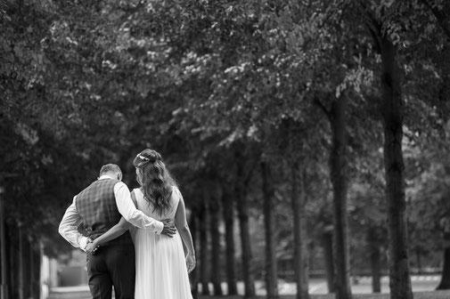 Ein Hochzeitspaar im Schlosspark des Schloss Philippsruhe Hanau. Es läuft die Allee entlang.