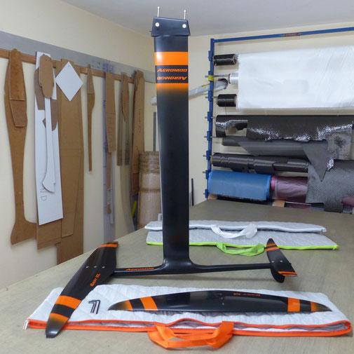windfoil aeromod v2 noir et orange, avec housse en tissu matelassé gris clair et orange, et deux autres housses gris-vert fluo et gris-blanc