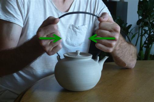 Consignes à faire pour retirer l'anse en fer forgé de la bouilloire.