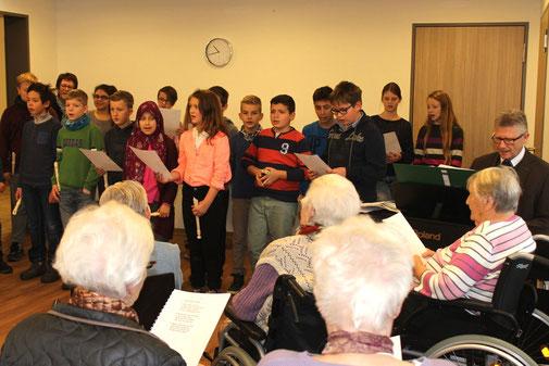 Alt und jung singen gemeinsam ein Weihnachtslied.