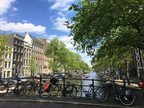 Amsterdam foto dal ponte vista canale con barche, biciclette e palazzi del centro città
