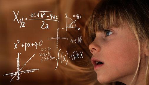 Petite fille blonde avec une frange qui regarde d'un air perdu des formules mathématiques.