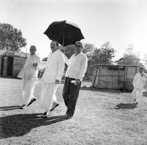 Baba holding Gustadji's hand, Adi K holding umbrella with Eruch following