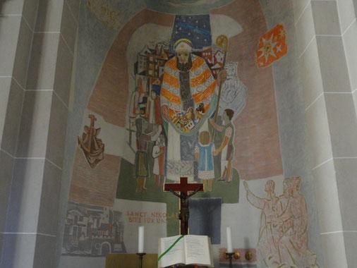 St. Nikolaus als Kinderfreund mit einem Sack voller Geschenke abgebildet. Er ist umringt von Mädchen und Jungen, die erwartungsvoll zu ihm aufschauen. Im Hintergrund gibt es weitere Indizien auf das Leben des Heiligen, vor allem auf sein Schifferpatronat.