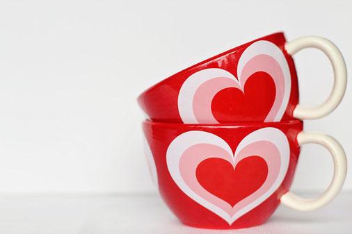 ハートが描かれた赤のマグカップが2つ、積み重ねられている。
