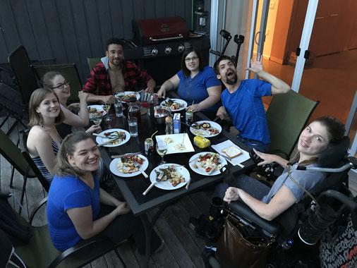 Groupe de personnes assis autour d'une table avec un repas et des breuvages sur une terrasse extérieure.