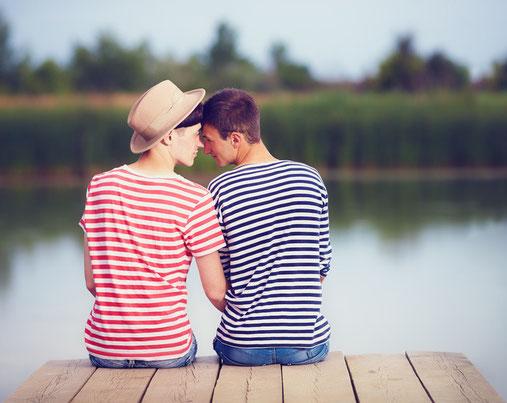 Abgebildet sind zwei Jungs, die glücklich auf einem Steg am See sitzen.