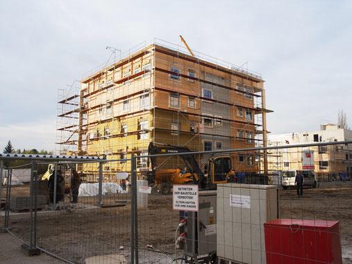写真3 木造の集合住宅 CLTの構造体、下から断熱材を施工中。階段室は鉄筋コンクリート