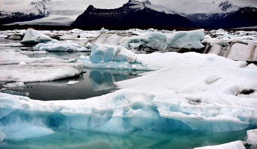 Eisbrocken, teils mit Vulkanasche beladen, treiben in der Lagune.