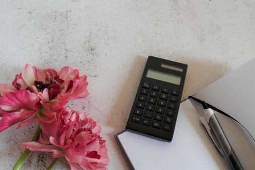 ノートと電卓。ボールペン。ピンクのアネモネ。