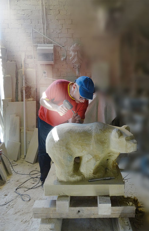 Bildhauer beim herstellen einer Bärenskulptur.