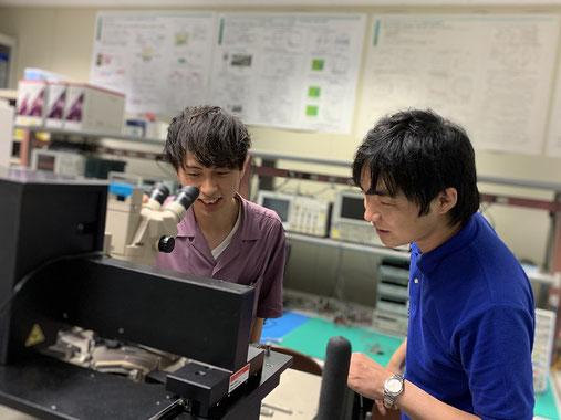 実験室の半導体プローバにて、学生の多田君と開発したコンピュータを評価している様子。 世界初の成果が得られる瞬間には代えがたい感動があります。