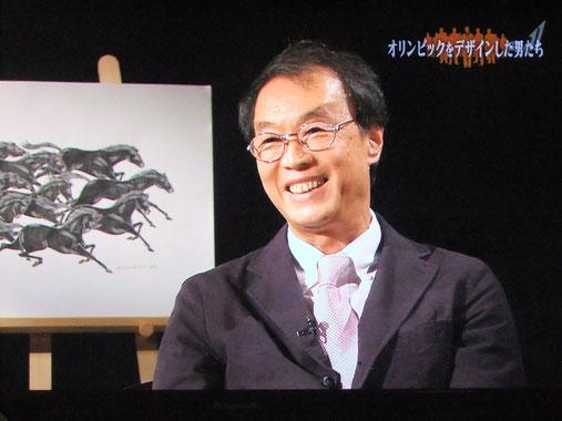 ※1964東京オリンピック当時のピクトグラム開発のようすを語る原田。うしろに見えるのは、原田の代表作のひとつ「馬九行久(うまくいく)の図」。直木賞作家の山本一力さんも大のお気に入りで、雑誌のインタビューなどでもわざわざ紹介していただいたりする作品です。