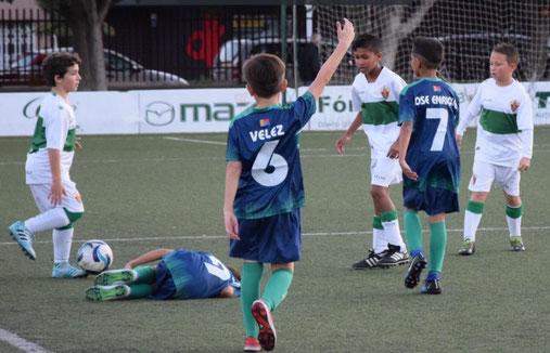 Imagen de unos jugadores en el campo de fútbol. Tres niños van con equipación color azul y verde y los otros tres de blanco y verde. Uno de los jugadores de azul y verde está tendido en el suelo tras recibir una entrada violenta,