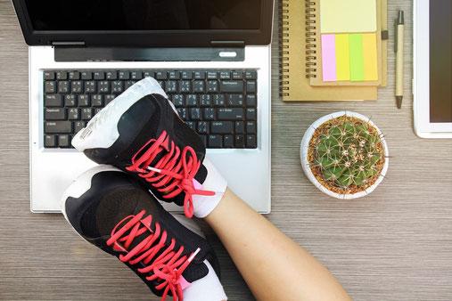 Beine mit Sportschuhen auf einem Schreibtisch mit Laptop und Arbeitsmaterialien