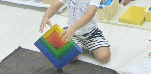 モンテッソーリの活動で、幼稚園児が集中して立体ブロックの活動に取り組んでいます