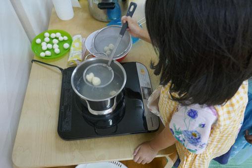 つき団子づくりで、幼稚園児がお湯で茹でた団子を網で上手にすくっています。