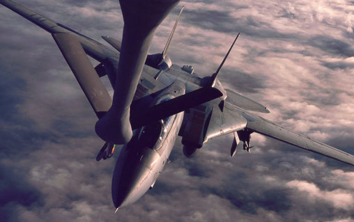 A US Navy F-14 takes on fuel over late-afternoon clouds.