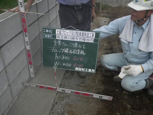 川越市笠幡地内の「土留ブロック及び駐車場築造工事」における重量ブロック積み工です。出来形(出来たもののサイズ)を測って記録しています。