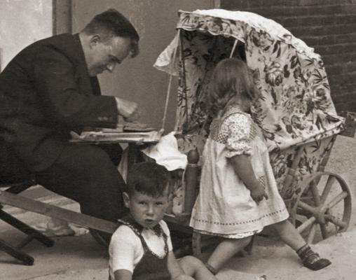 """Erwin Bowien in Egmond aan Zee im Jahr 1937. Am Strand malt er ein Kind im Kinderwagen im Rahmen des Zyklus """"Egmondse Kinderportretten"""" die heute größtenteils in der Sammlung des Niederländischen Königshauses verwahrt werden."""