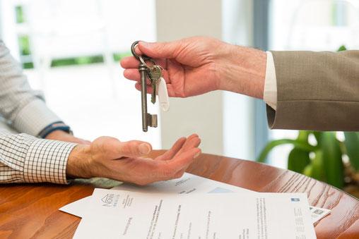 Schlüssel wird vom Makler an den Klienten überreicht