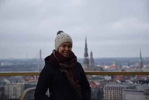 Greta Hartmann vor der Stadtkulisse von Riga