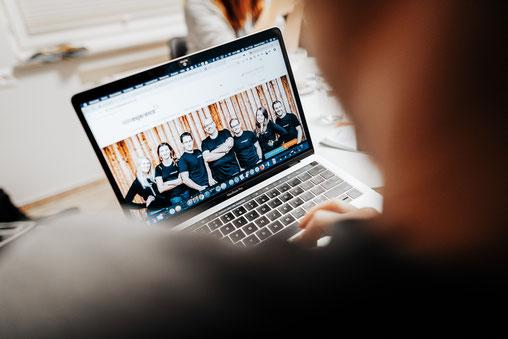 Laptop mit einem Teambild von Online Experience