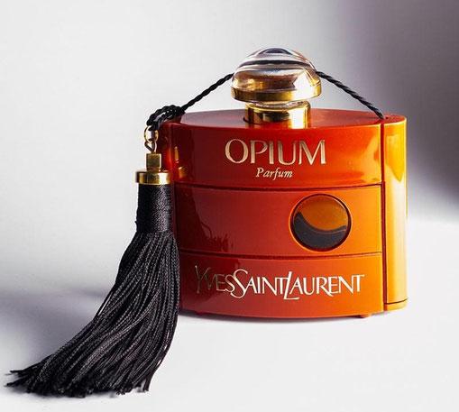 1977 -  OPIUM - PARFUM : SUPERBE FLACON  ECHASSE DANS UNE COQUE EN PLASTIQUE, AVEC FLOCHE EN SOIE NOIRE - DESIGN MR PIERRE DINAND