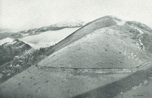 Der mit Granattrichtern überzogene Mt. Kuk. Im Hintergund der Gipfel des Mt. Matajur im Oktober 1917. Im Vordergrund verläuft die italienische Versorgungsstraße.