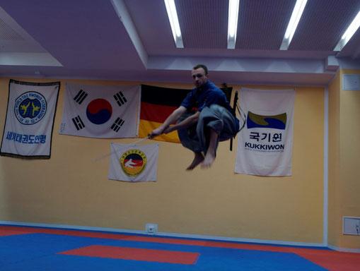 Heidong Gumdo-Meister spingt in die Luft und schlägt mit seinem Schwert.