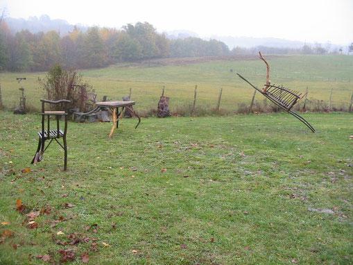 Trois meubles en châtaignier (une chaise, une table, un banc) qui semblent courir car certains de leurs pieds ne touchent pas le sol