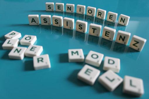 Text: Senioren-Assistenz - Plöner Modell mit Scrabble Steinen dargestellt.