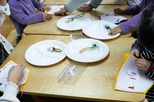幼児教室のクリスマス会で年少児がクリスマスの製作でフォトフレームを制作しています。