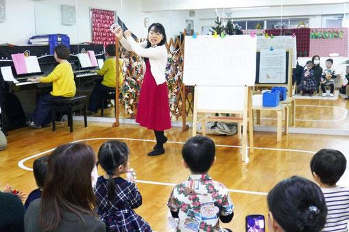 2歳児・母子分離クラスのお友だちがクリスマス会のリトミックで、音楽に合わせて楽器を鳴らしています。