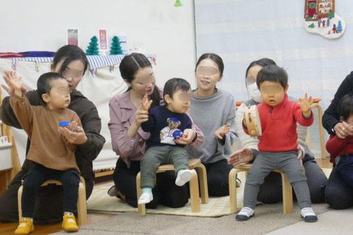 幼児教室のクリスマス会で、0歳児と1歳児が好きな楽器を選んで、ピアノに合わせて楽しく鳴らしています