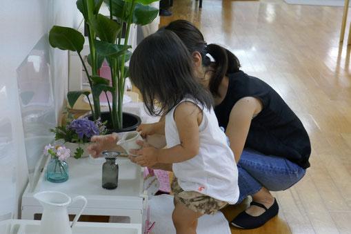 モンテッソーリ活動の生花のお仕事で、1歳字が集中して、花瓶に水を注いでいます。