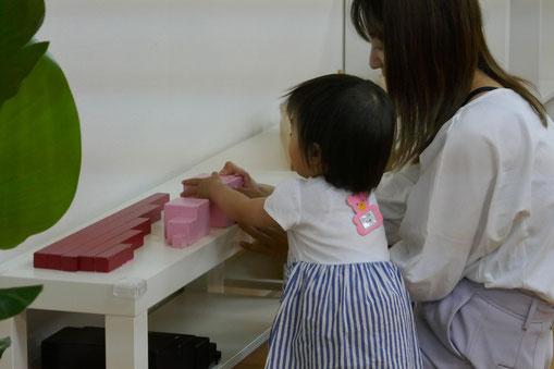 1歳児が感覚教具の中のピンクタワーの活動に取り組んでいます。