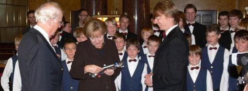 Ein Präsent für die Kanzlerin - Chorleiter Roman Twardy überreicht Angela Merkel im Kurhaus die Jubiläums-CD